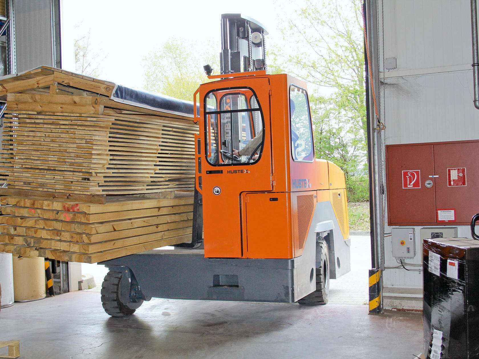 Fourway sideloader carrying timber pack